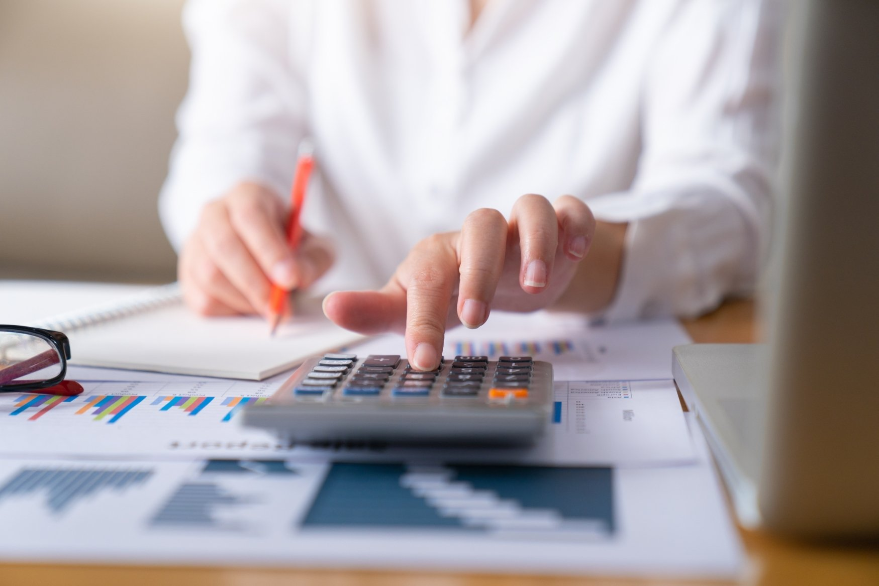 Woman using a calculator to create a budget