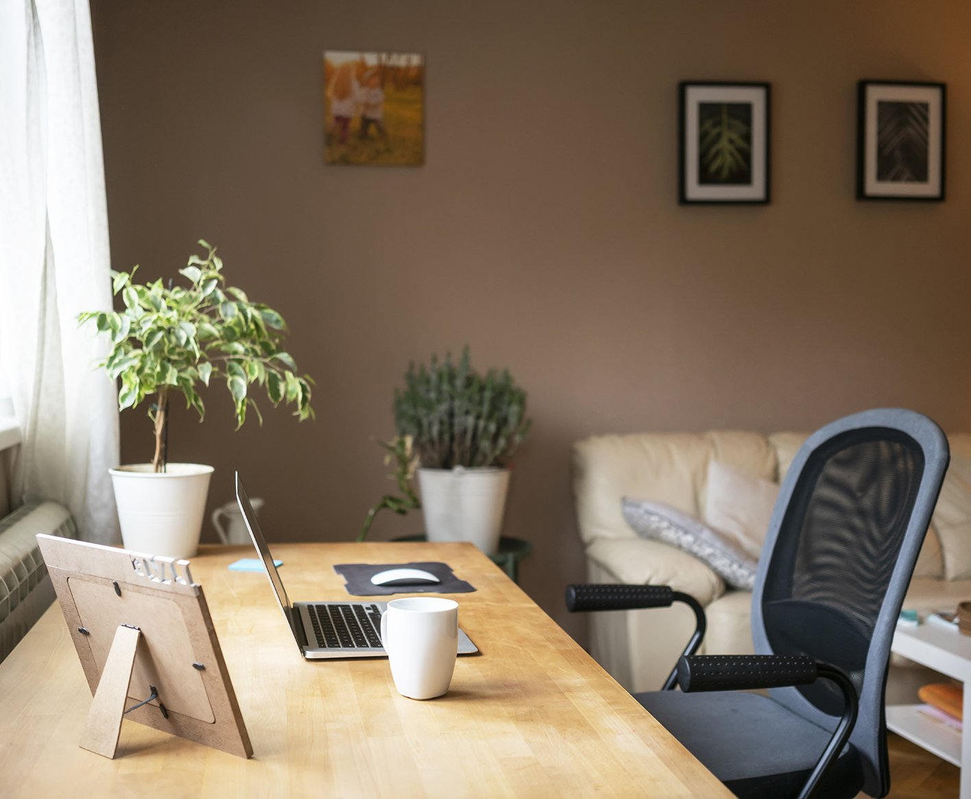 desk chair and laptop on a desk in a home office space