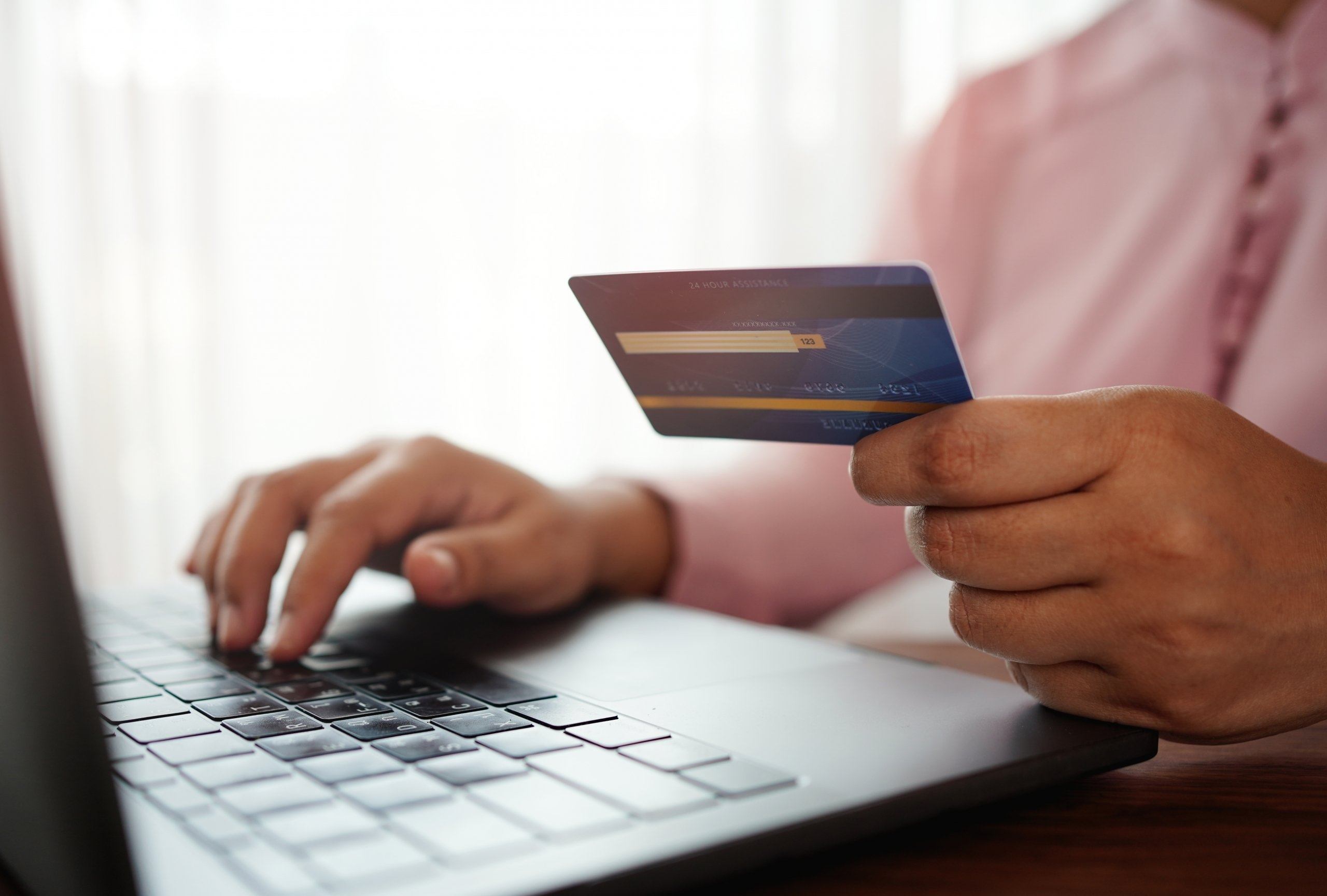 man holding a credit card while making an online purchase on a laptop