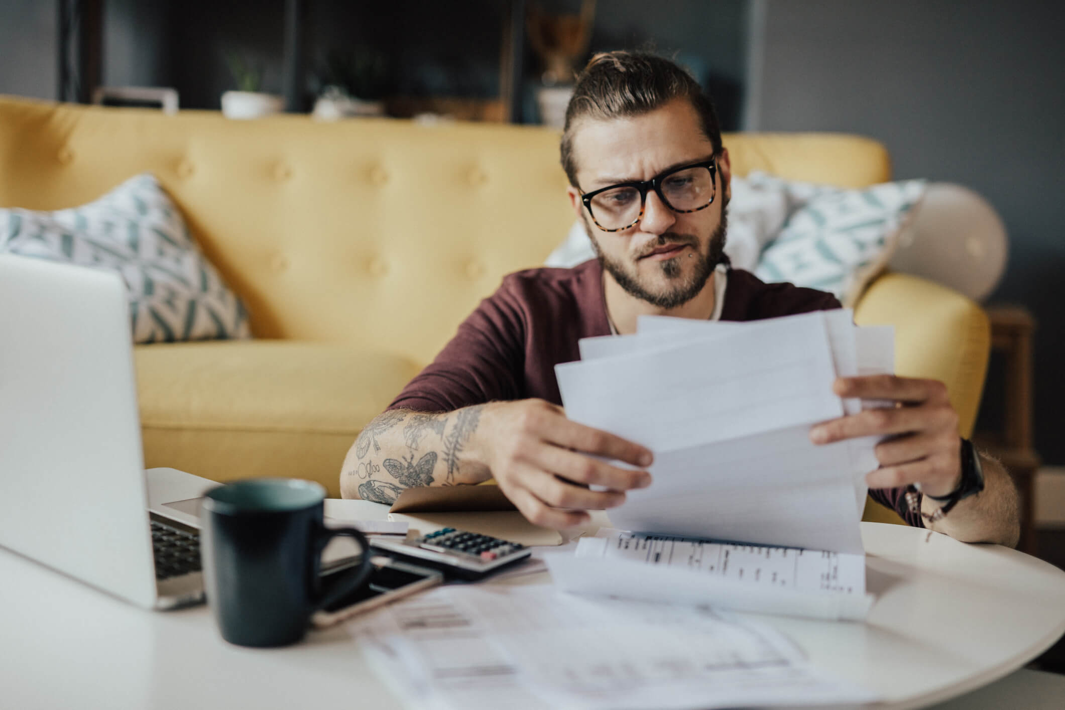 millennial looking at bills while sitting at laptop