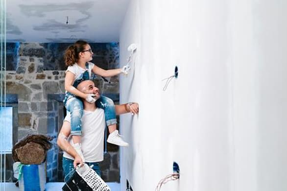 father and daughter painting a wall together while fixing up their home
