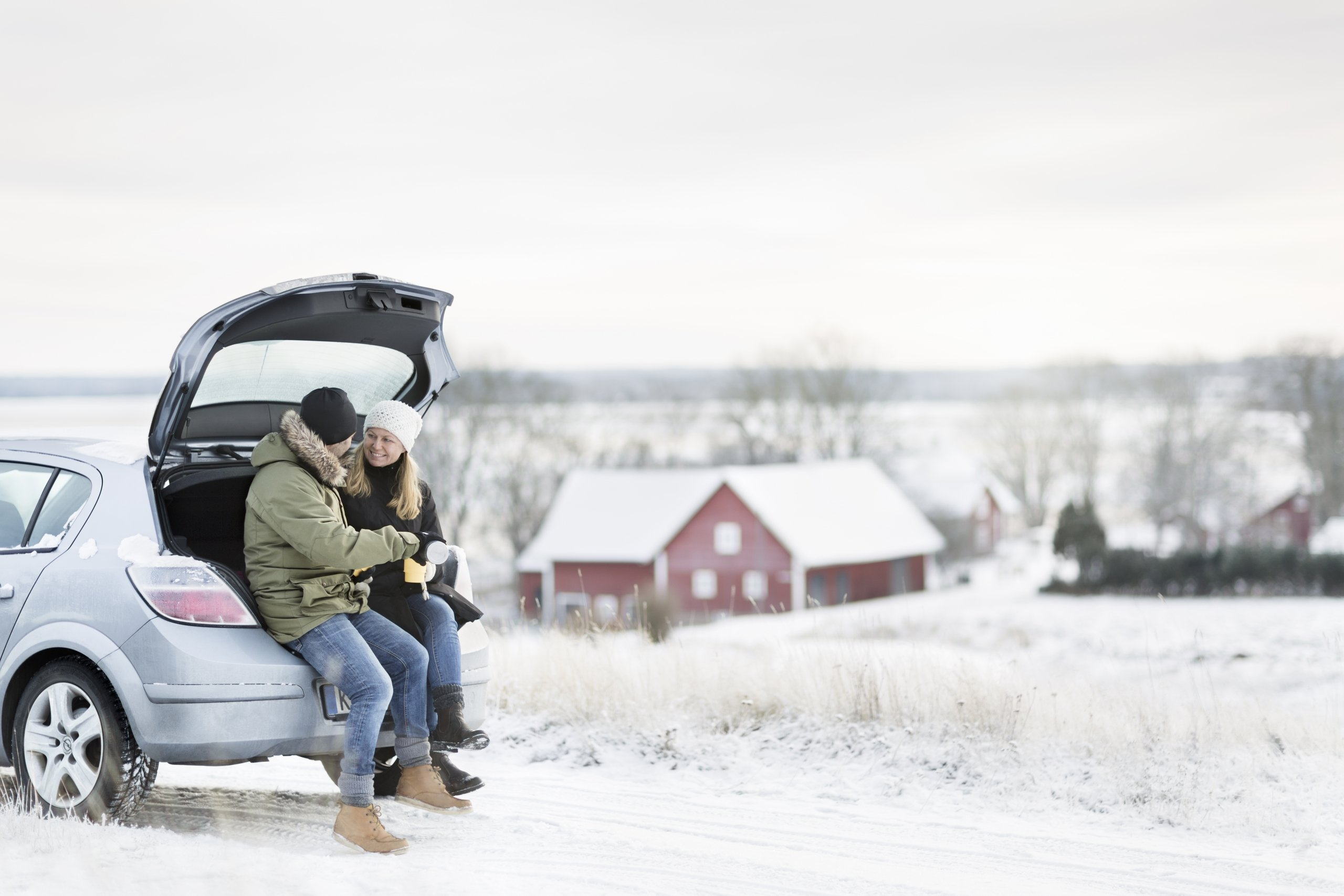 Couple sitting on the trunk of car during winter
