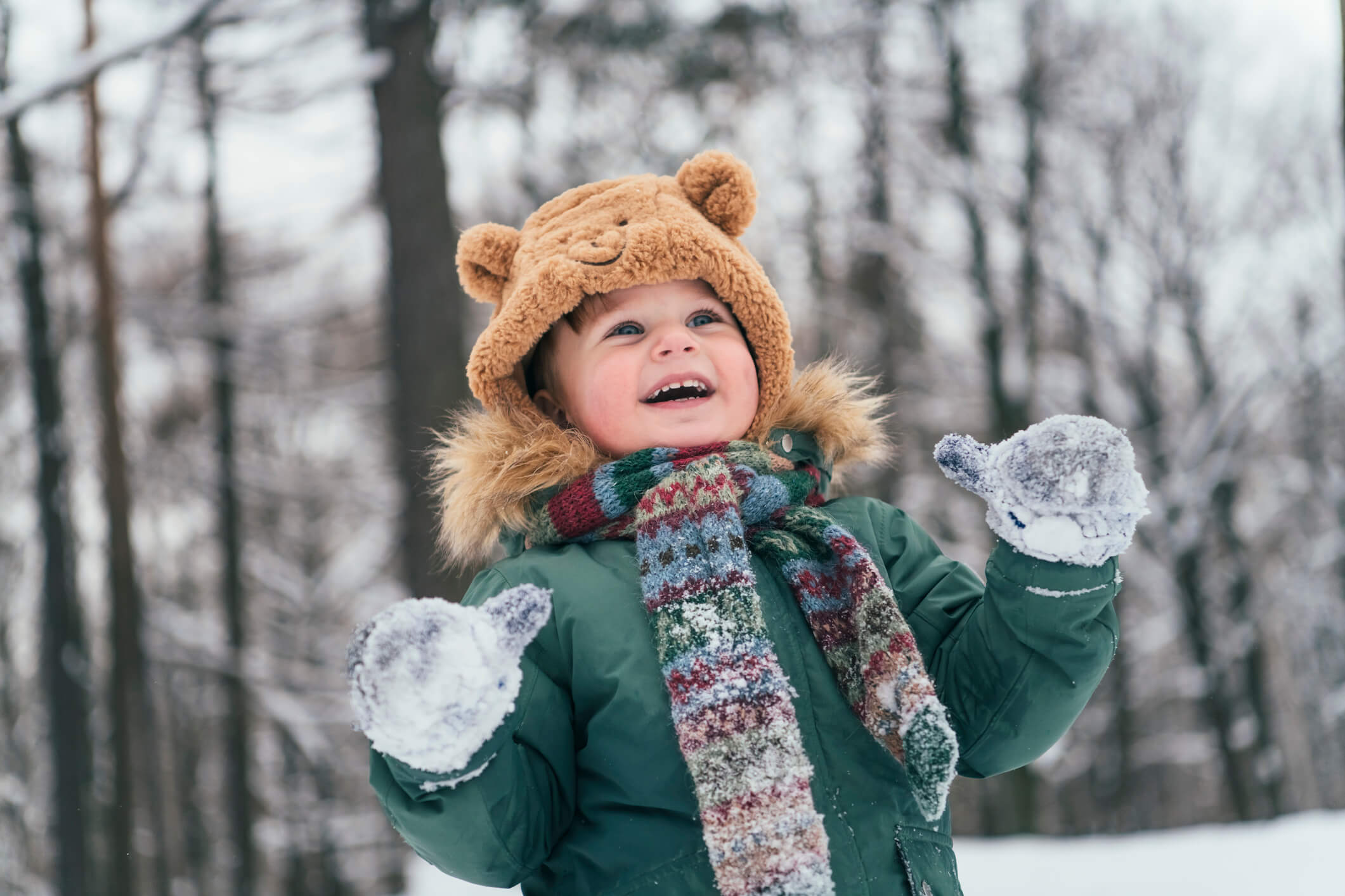 toddler with snowy mittens and a bear hat in the woods