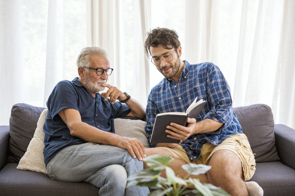 Older man and younger man sitting on sofa having a conversation