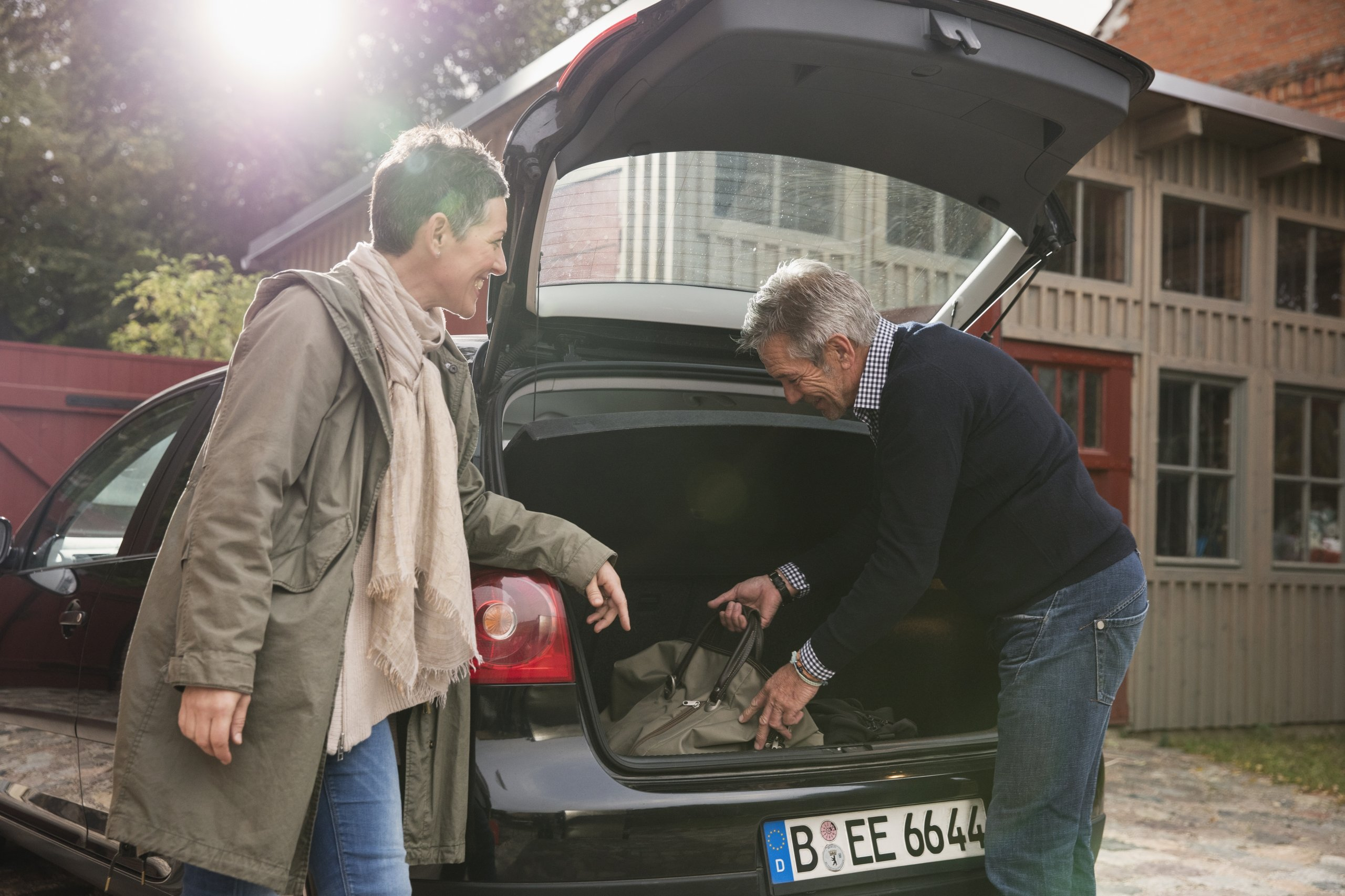 A couple reaching inside the trunk of their car