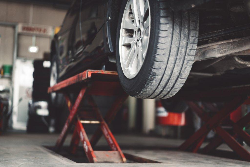 Black car lifted inside a repair shop