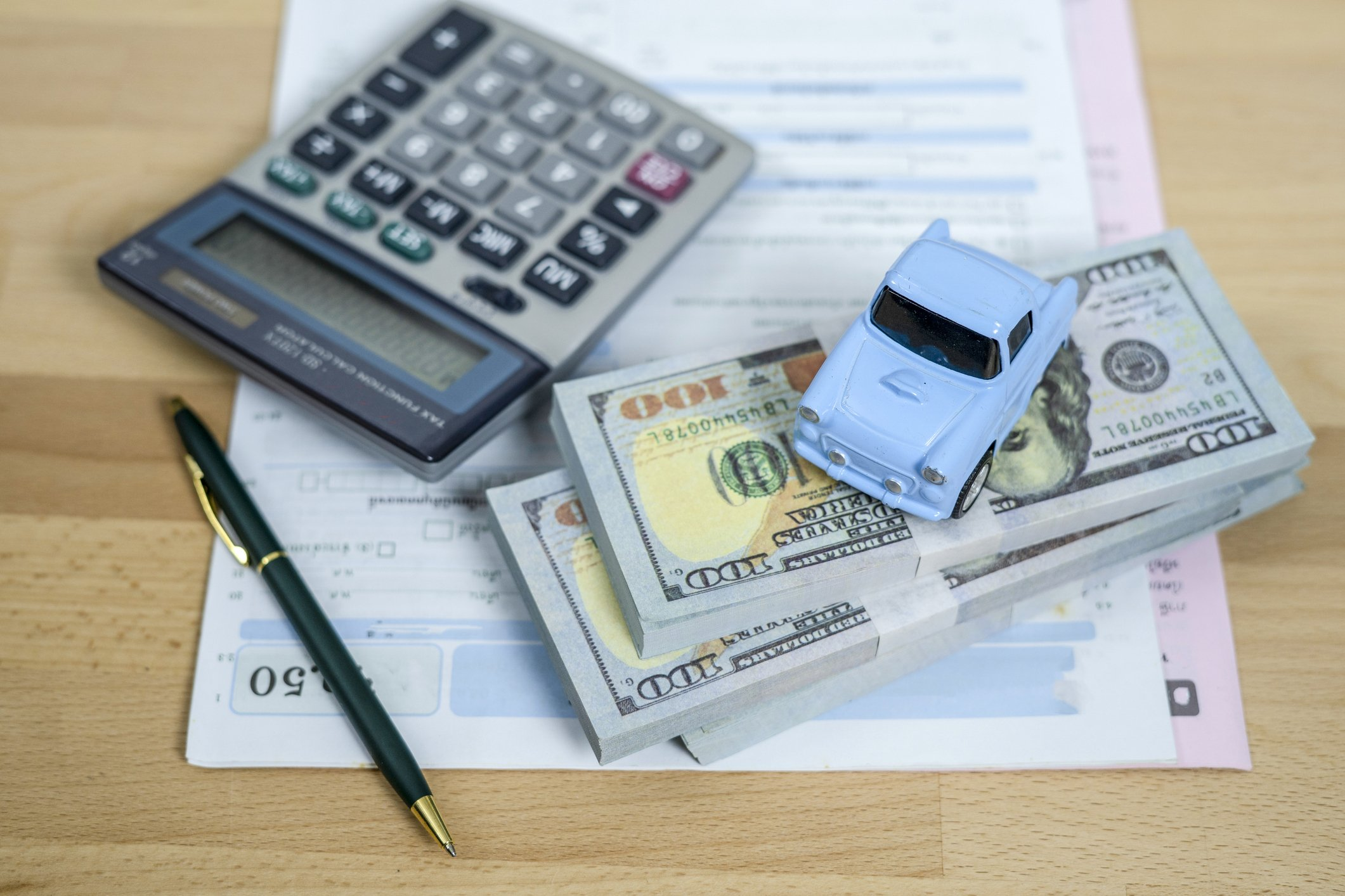 Calculator and stack of money to pay for car expenses