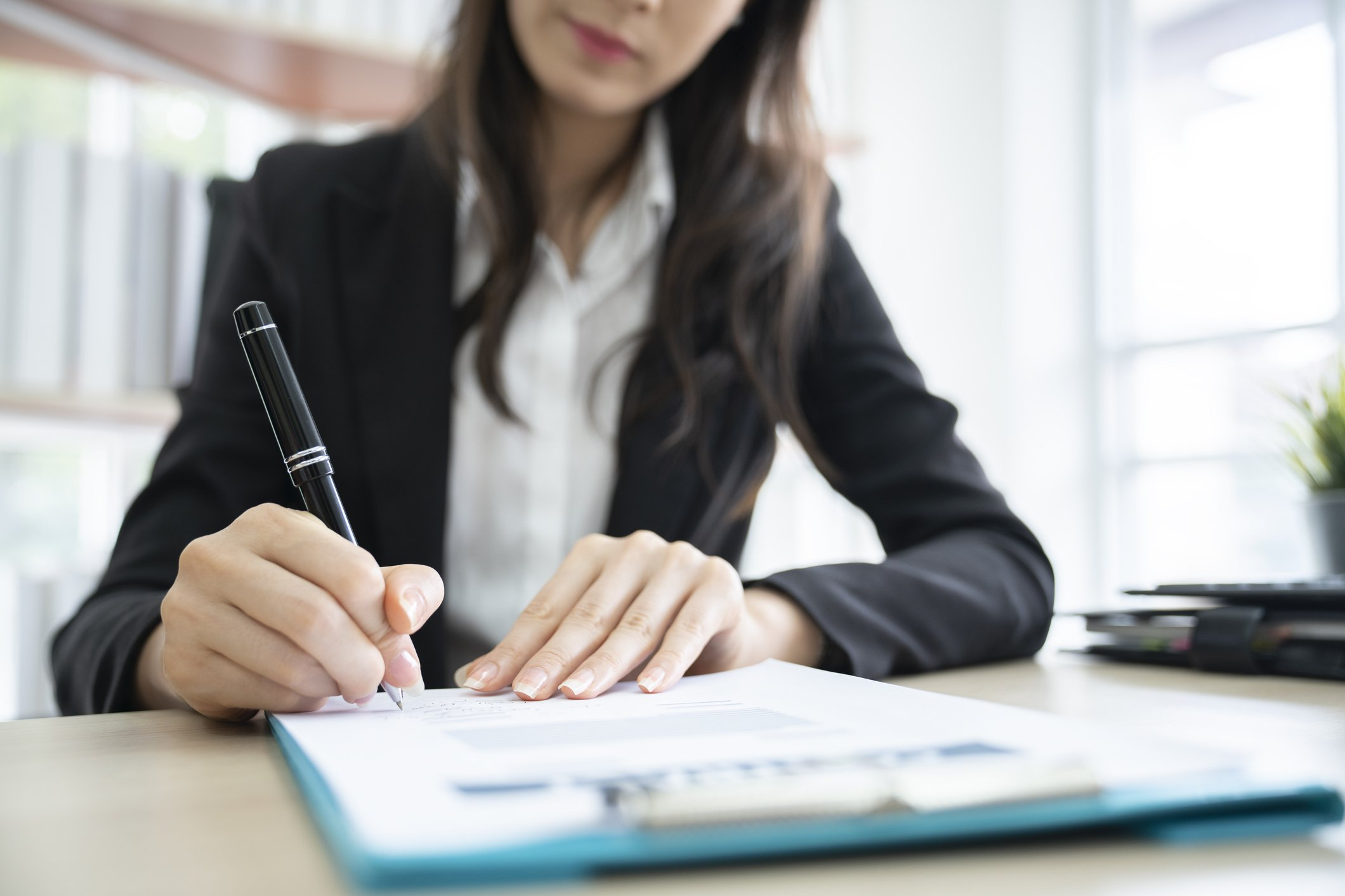 Woman signing loan documents