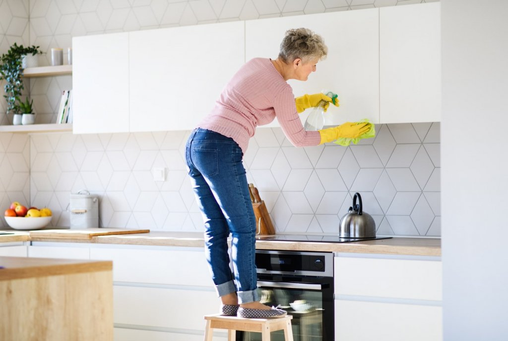 A woman cleaning kitchen cabinets