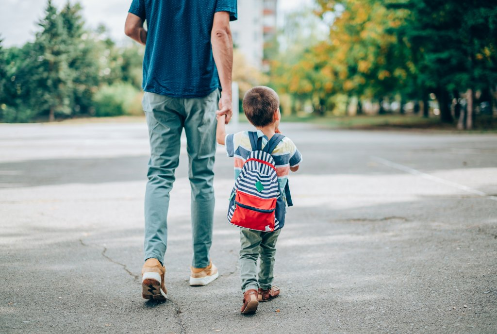 Father walking son to elementary school
