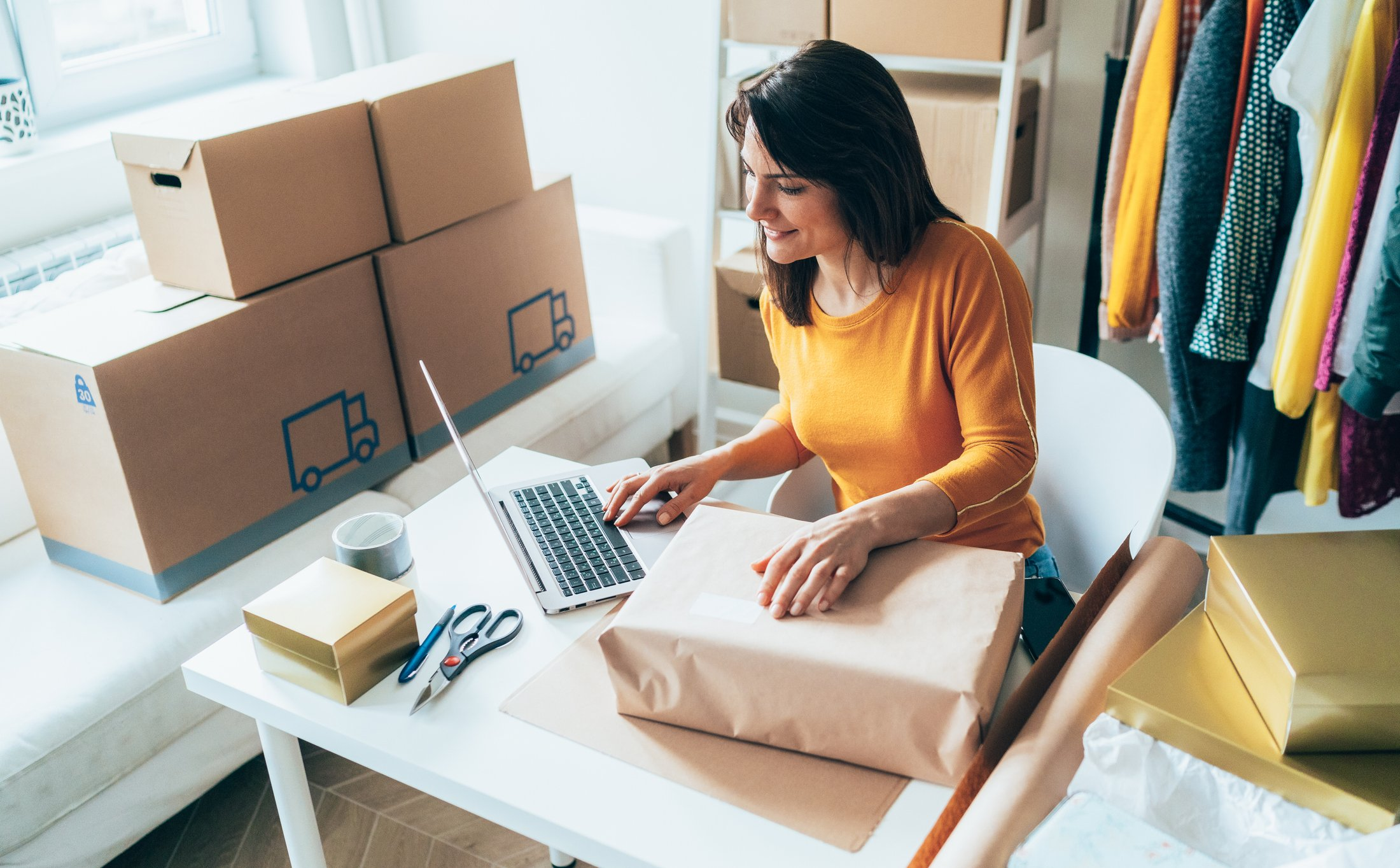 An entrepreneur sitting at a desk managing shipping, processing orders, and packing boxes.
