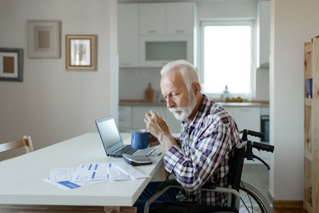 A person sitting at a table with a computer and papers on it