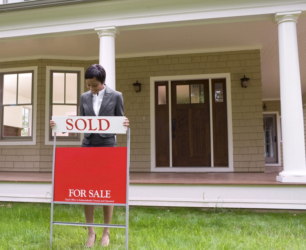 A Real Estate agent adding a sold sign to house front yard